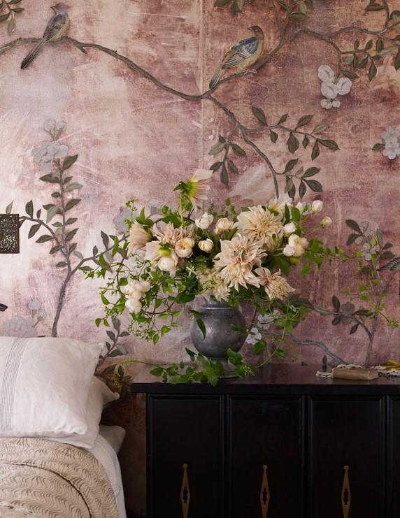 dettaglio di comodino nero in camera da letto con fiori e carta da parati a fiori rosa