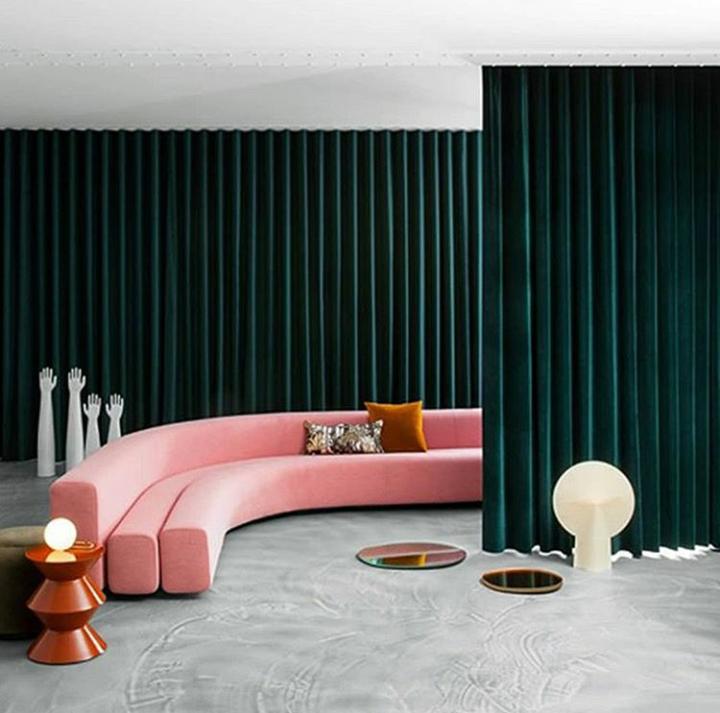 Pouf in velluto rosa con struttura in oro, lampadario a sfera moderno e tende in velluto