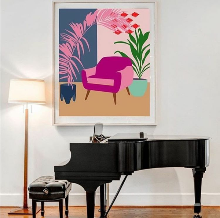 quadro con poltrona rosa su parete bianca, con pianoforte nero in primo piano