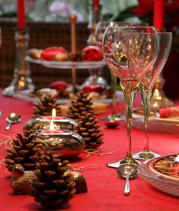 idee per apparecchiare la tavola di Natale in rosso con le pigne