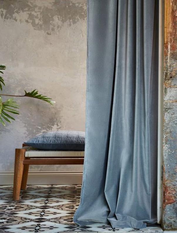 tende azzurre con pavimento di cementine e sgabello di legno