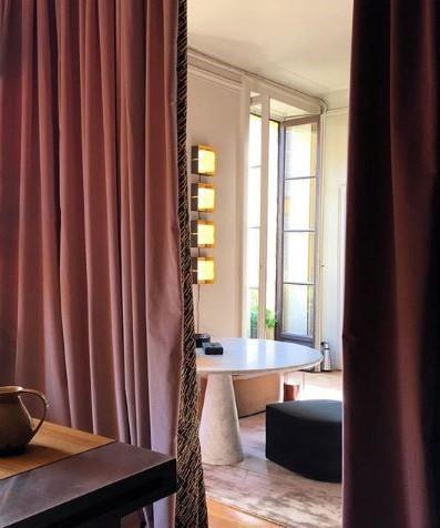 Tende rosa di velluto su soggiorno in stile industriale con tavolo rotondo bianco